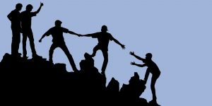 Silhouette of a group helping one another climb a rocky outcrop. Harm reduction