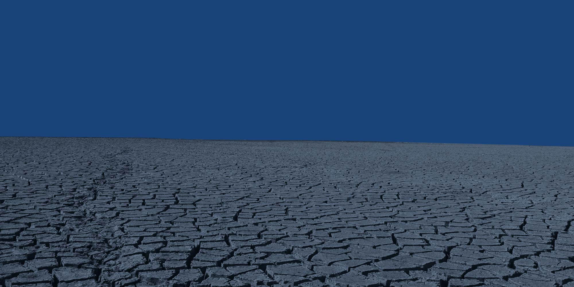 Dry, cracked earth of an empty river bed. Intermittent reinforcement.
