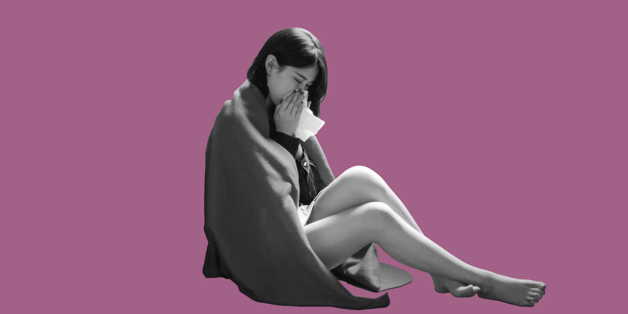 A woman wrapped in a blanket blowing her nose. Staying sober when you're sick.
