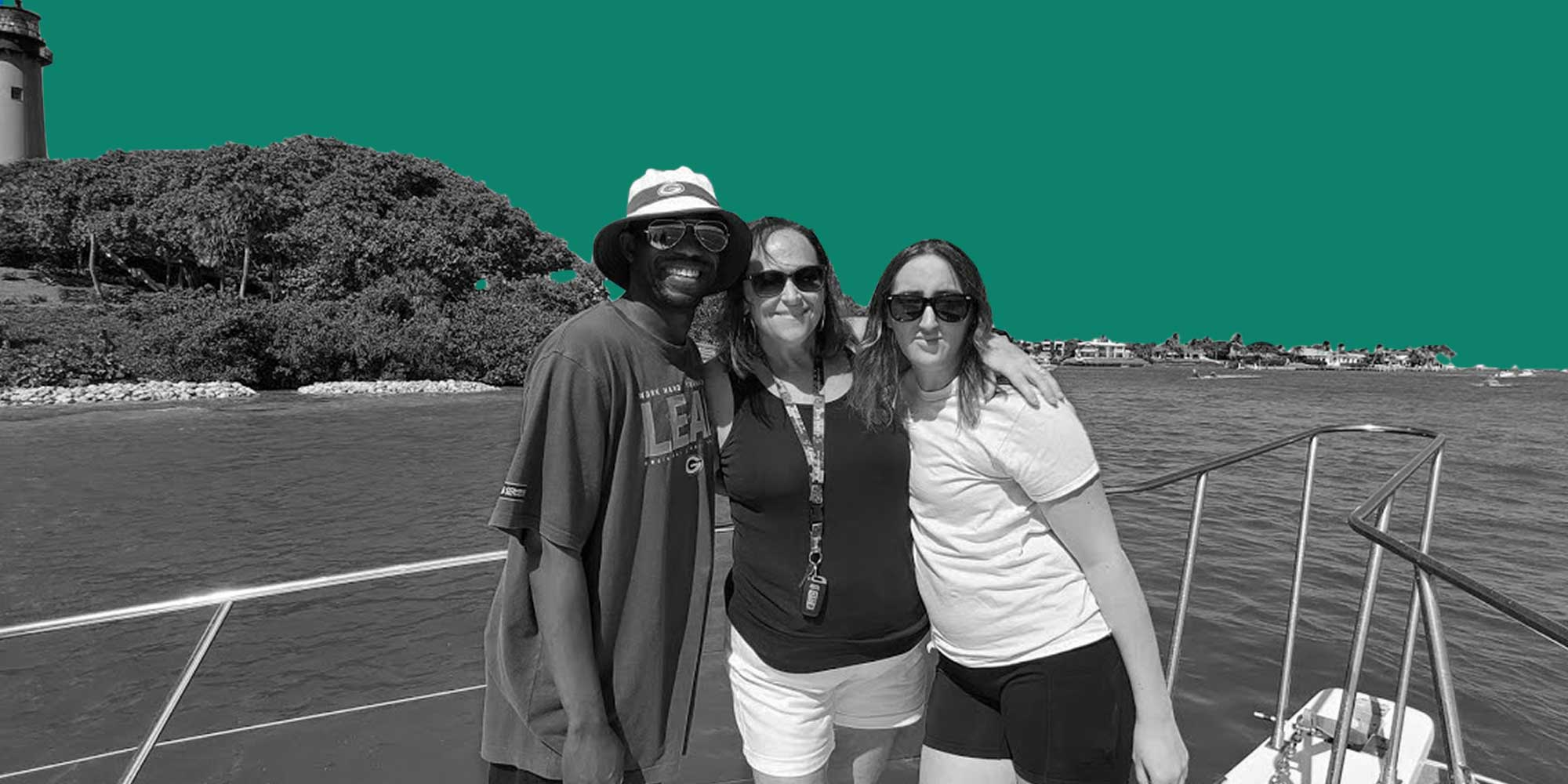 A family of one African American man and two White women on a boat