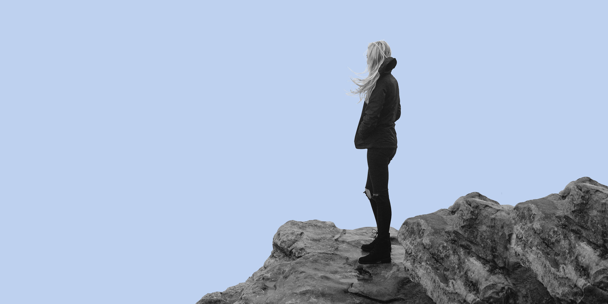 Woman alone on rocks. Does alcohol make anxiety worse?