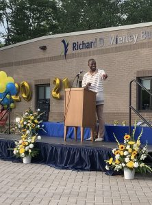 Freddy Shegog standing at a lectern on an outdoor stage, addressing the class of 2021.