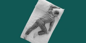 A man sleeping spread face-down across his bed. Treat insomnia without drugs