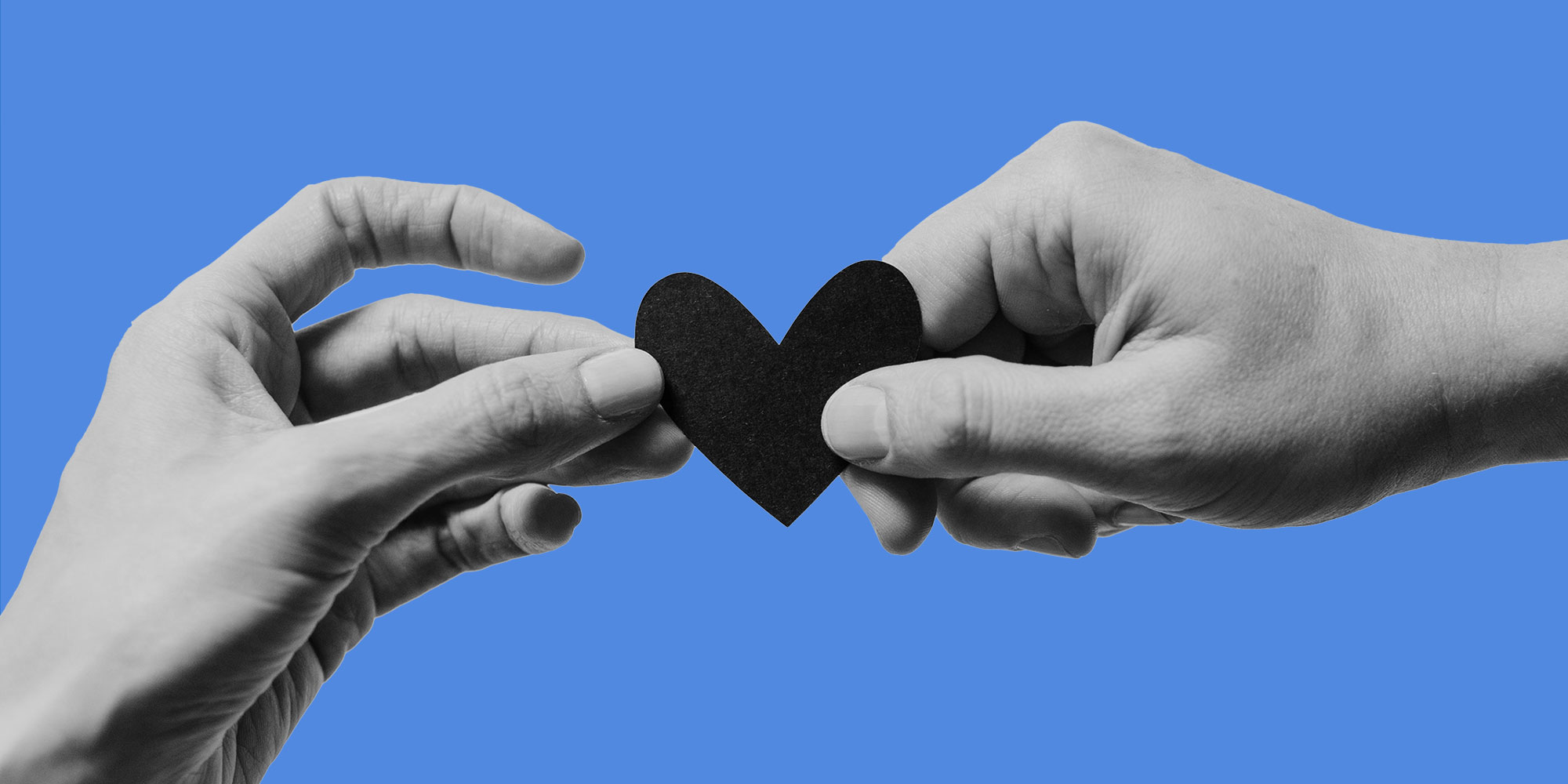 Two hands holding a paper heart. Dating in recovery