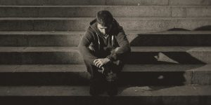 Man in a hoodie sitting sadly on outdoor stairs. Does withdrawal cause depression?